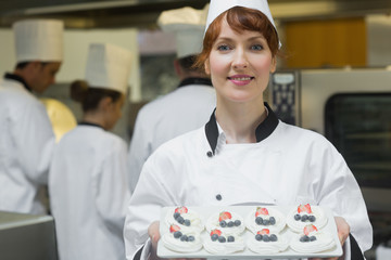 Happy female chef presenting plate of meringues