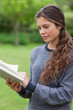 Young relaxed adult reading a book in the countryside