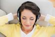 Peaceful casual brunette in yellow cardigan enjoying music