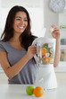 Gorgeous woman using a blender while standing