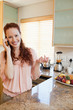 Woman on the phone next to the kitchen counter