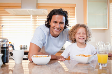 Father and daughter having cereals in the kitchen together