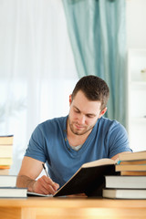 Male student preparing book report