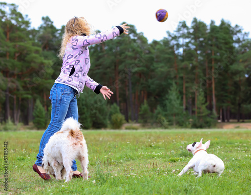 woman throws  ball to the dog
