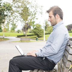 Man sitting in the wooden bench and working with computer.