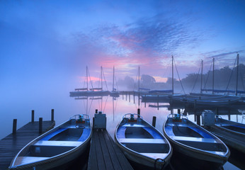 Purple and blue, foggy dawn at a small harbor.