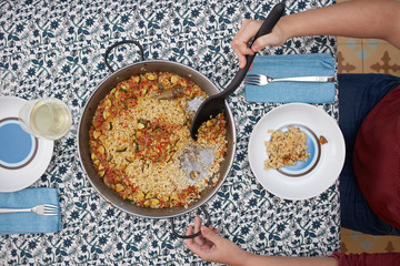 Woman's hands serving rice on a dish