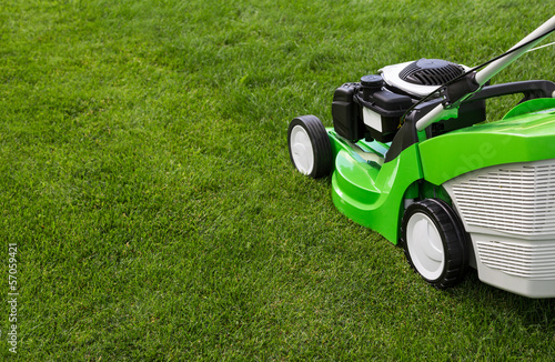 Green lawnmower on green lawn