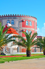 Beautiful building made of red brick and green palms