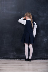 schoolgirl leaning her forehead against blackboard