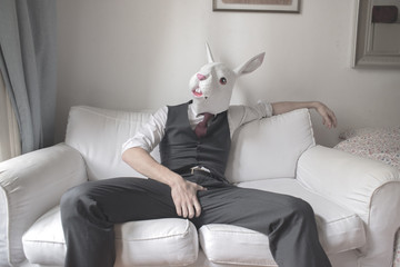 rabbit mask man sitting on sofa