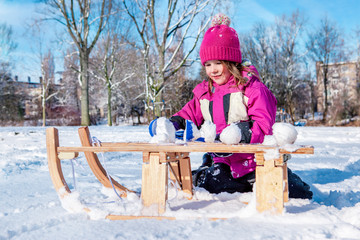 Preschool girl making snowballs
