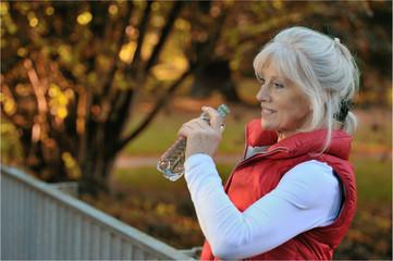 Sportliche Seniorin erfrischt sich mit Mineralwasser
