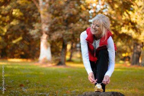 canvas print picture Aktive Seniorin bindet Sportschuh zu