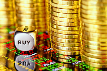 Golden coins, financial chart and dices cube with the word BUY.