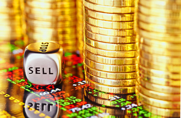 Golden coins, financial chart and dices cube with the word SELL.