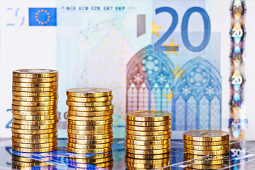 Downtrend stacks of golden coins and euro banknote as background