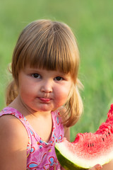 Portrait of the child who eats a sweet water-melon