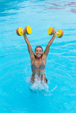 Woman is engaged aqua aerobics with dumbbells in water