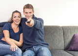 Couple watching television pointing remote control