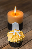 Halloween pumpkin cupcake and a burning candle