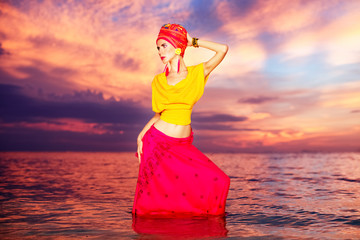 Portrait of a girl in oriental style on the beach at sunset