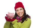 Mixed Race Woman Wearing Winter Hat Holding Piggybank on White