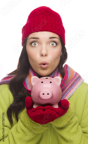 Expressive Mixed Race Woman Wearing Winter Hat Holding Piggybank