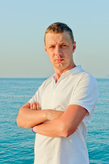 portrait of a man in a white shirt against the sea