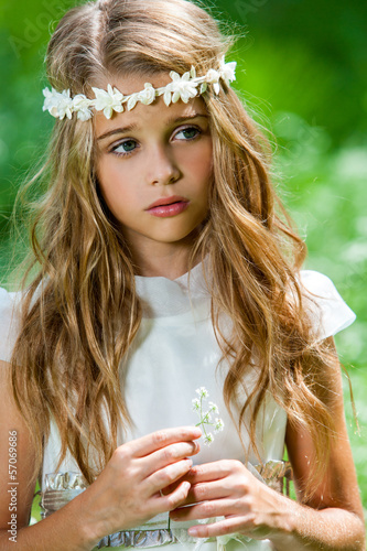 Cute girl in white dress holding flower.