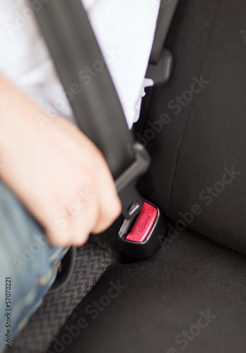 man fastening seat belt in car