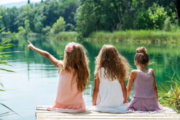 Three girl friends together on river jetty.
