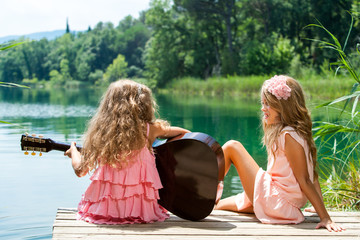 Young girls singing together with guitar.
