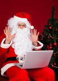 Portrait of santa looking at laptop