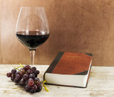 old book and red wine with grapes on table