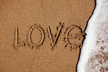 Word love on the beach is washed off with water