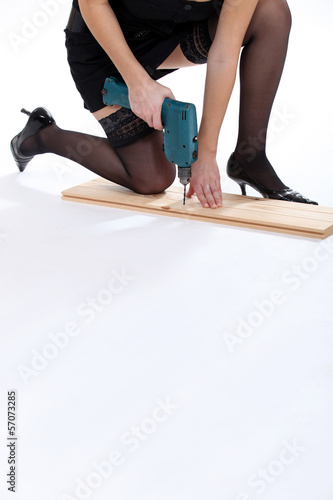 Attractive woman using drill whilst kneeling