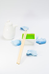 White bottle dish for sauce and green liquid with chopsticks