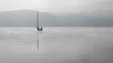lake at dawn sailing boat in fog mountains in the back