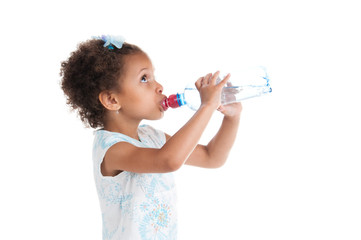The little mulatto girl drinks water from a bottle.