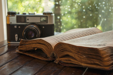 Retro camera and old book on wooden table