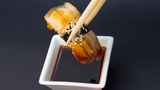 Smoked eel sushi nigiri in chopsticks with soy sauce