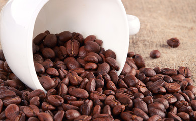 Coffee cup and grain on background