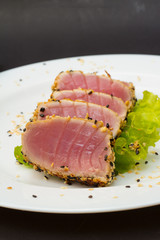 Tuna fillet on white dish with sesame salad and soy sause