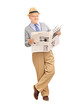 Senior gentleman reading a newspaper and leaning against a wall