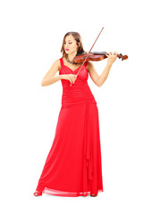 Young attractive female in red dress playing the violin