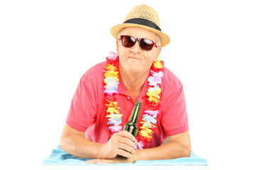 Happy mature man lying on a beach towel and holding a beer