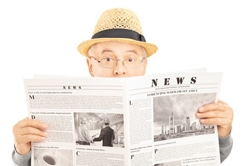 Scared senior man with glasses hiding behind a newspaper