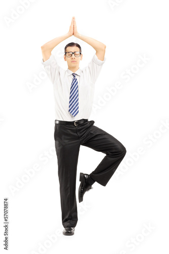 Full length portrait of a young businessman meditating