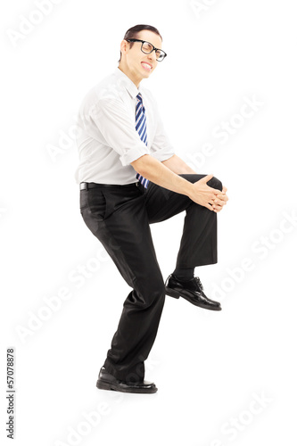Full length portrait of a young man holding his knee because of
